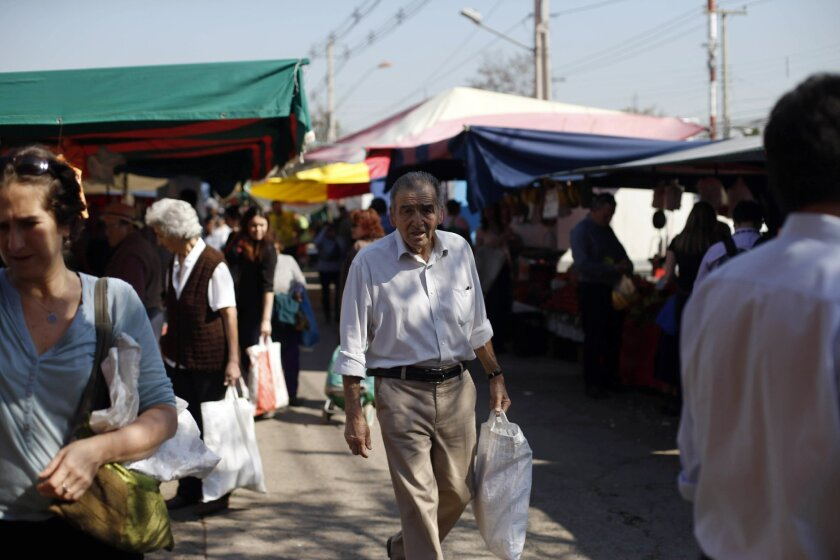 In this Sept. 3, 2015, photo, a man walks in a traditional wet market in Santiago, Chile. Like many shoppers in emerging countries, Chileans like to find fresh fruits and vegetables daily at open markets. In recent years, Wal-Mart has been pushing more frozen food to appeal to working Chilean women