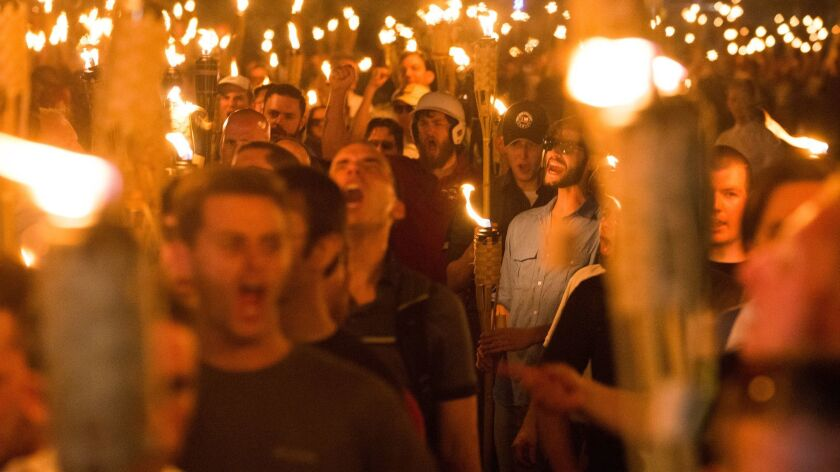 "A white supremacist march proceeds through the University of Virginia campus the night before the ""Unite the Right"" rally in Charlottesville, Va., in 2017."