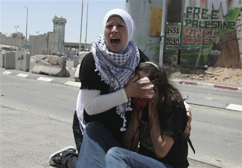 A Palestinian woman reacts as she holds a cloth to the bleeding face of an American activist who was wounded during clashes with Israeli troops at the Kalandia checkpoint between the West Bank city of Ramallah and Jerusalem, Monday, May 31, 2010.  The clashes erupted during  a protest against Israe