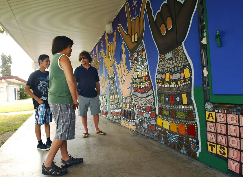 Rob Tobin,  Artist-in-Residence at A Reason To Survive (ARTS), right, with Sebastian Gonzalez, left, and Dylan Ginther look at a mural they helped make in honor of their friend and fellow student Yusra Nasir who passed away last year. The multi-dimensional mural lines a wall at Lafayette Elementary