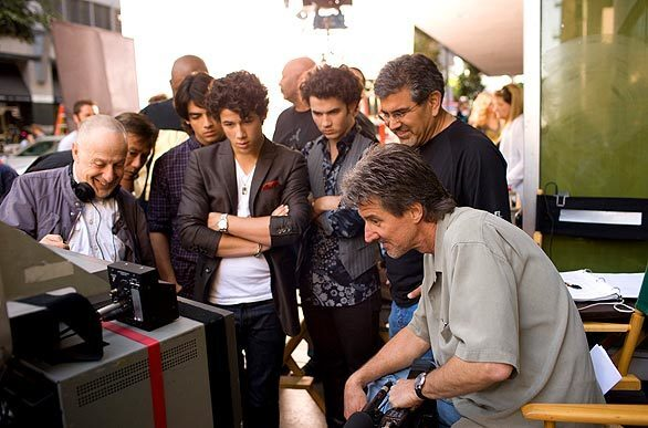 """So, how did that look? The siblings watch playback while at work with director Bruce Hendricks, seated at right, on """"Jonas Brothers: The 3D Concert Experience."""""""