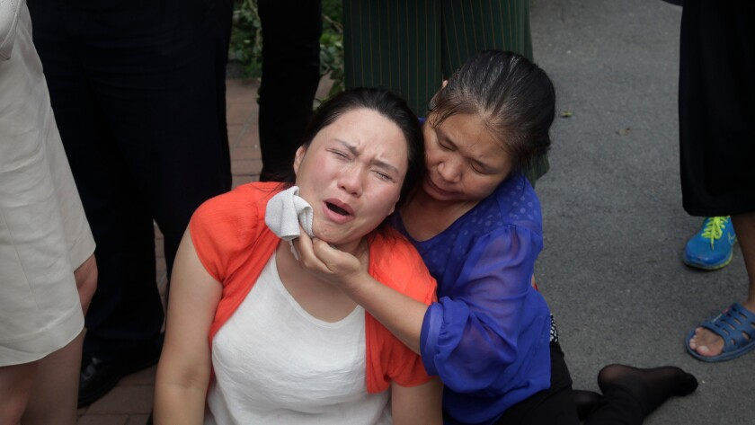 Fan Lili, left, the wife of imprisoned lawyer Gou Hongguo, cries as she is comforted after an incident with plainclothes police outside the Tianjin No. 2 Intermediate People's Court in Tianjin, China, on Aug. 1, 2016.