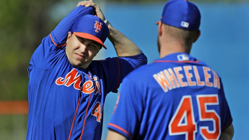 Mets pitcher Jacob deGrom, left, talks with teammate Zack Wheeler while stretching during spring training baseball practice, Thursday, Feb. 14, 2019, in Port St. Lucie, Fla.