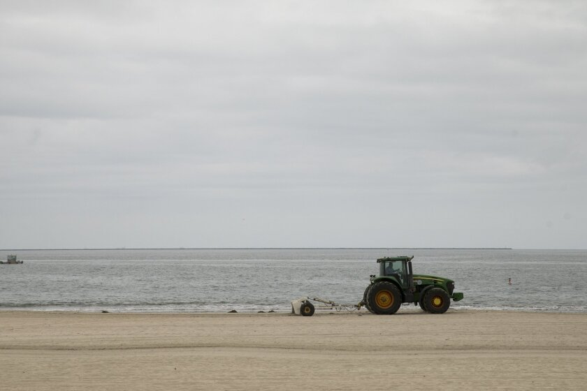 A tractor rakes up the debris on the beach, Thursday, June 4, 2015, in Long Beach, Calif.  A 4-mile stretch of a Los Angeles-area beach was closed Thursday to swimmers and surfers after tar balls washed ashore — the latest Southern California coastline to shut down due to oily goo, authorities said