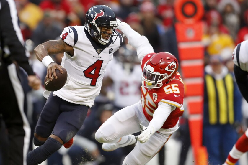 Texans quarterback Deshaun Watson scrambles away from Chiefs defensive end Frank Clark during the second half of an AFC divisional playoff game on Jan. 12.