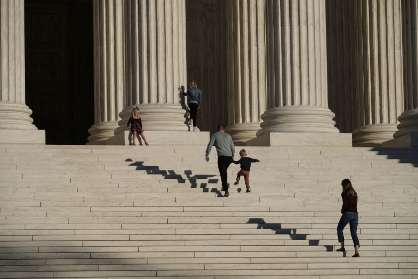 A family visits the Supreme Court in Washington, Wednesday, Nov. 4, 2020. The Trump campaign is seeking to intervene in a Pennsylvania case at the Supreme Court that deals with whether ballots received up to three days after the election can be counted. (AP Photo/J. Scott Applewhite)