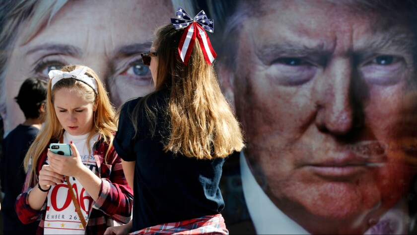 People pause near a bus adorned with large photos of candidates Hillary Clinton and Donald Trump before the presidential debate at Hofstra University in Hempstead on Monday.