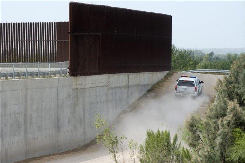 Un vehículo de la Guardia Fronteriza patrulla junto a la valla de protección paralela al Río Grande cerca de McAllen