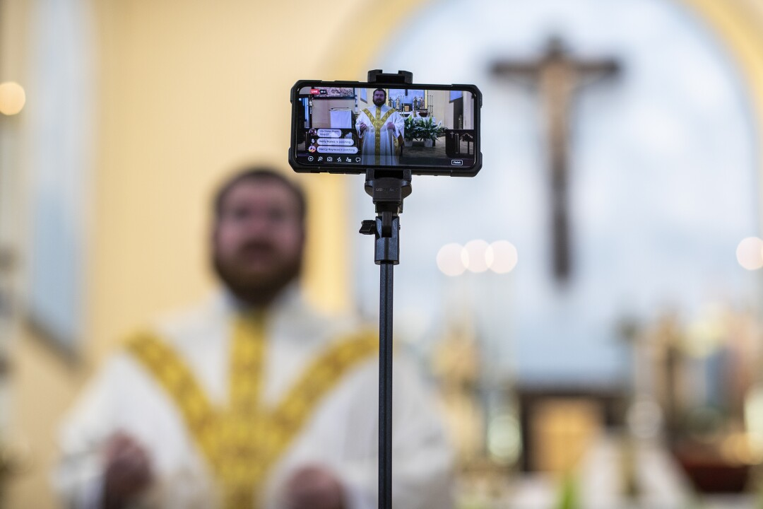 The Rev. Kristopher Cowles uses a phone to broadcast a homily from Our Lady of Guadalupe in Sioux Falls.