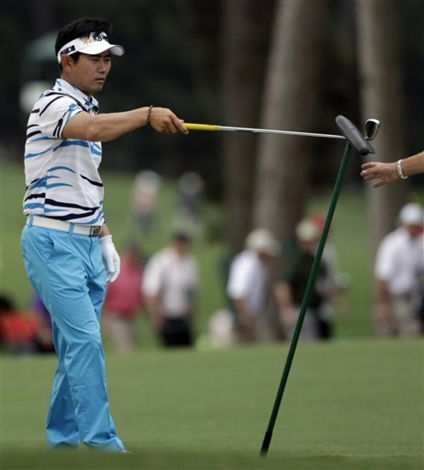Y.E. Yang, of South Korea, hands over a rake with his club to a caddie on the first hole during the second round of the Masters golf tournament Friday, April 12, 2013, in Augusta, Ga. (AP Photo/Darron Cummings)