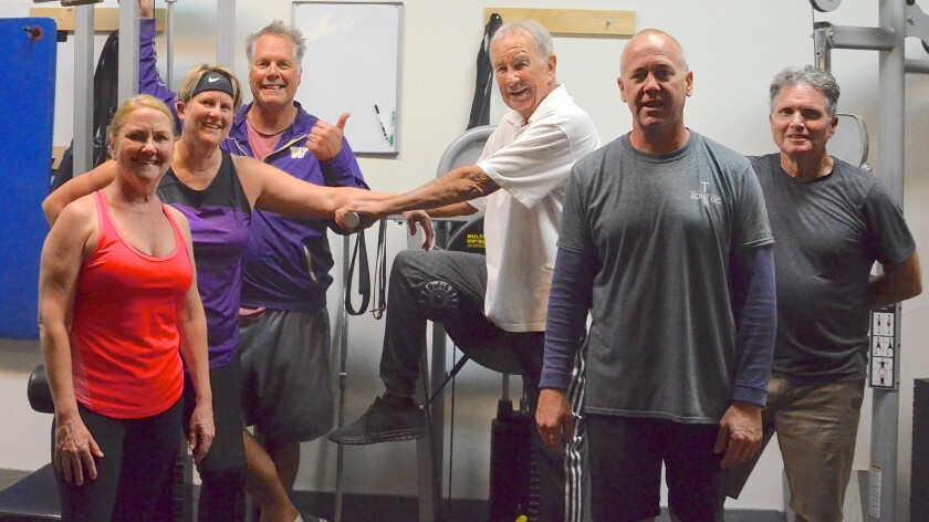 Kristi Peckham, Lea Campbell, Neil Ross, Harold Graham, 85, instructor Trevor Duncan and Brian Carroll, from left, attend a group personal training class at the Training Zone in Costa Mesa.