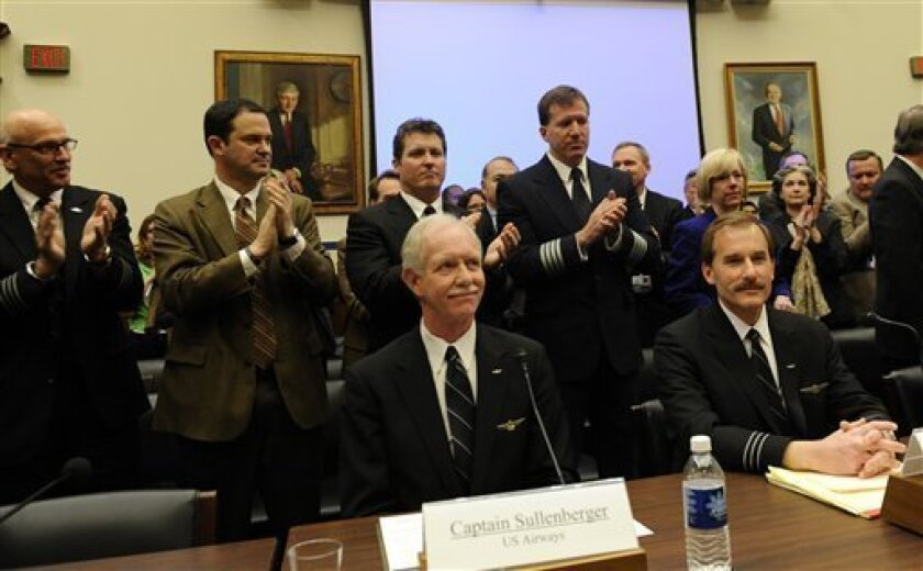 US Airways flight 1549 Capt. Chesley B Sullenberger III, seated, center, and First Officer Jeffrey B. Skiles, seated, right, receive a standing ovation on Capitol Hill in Washington, Tuesday, Feb. 24, 2009, as they prepared to testify before the House Transportation and Infrastructure Committee. (AP Photo/Susan Walsh)