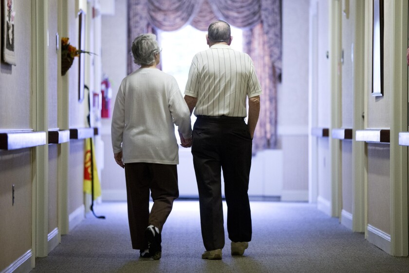 A woman with Alzheimer's disease walks with a companion in a nursing home.