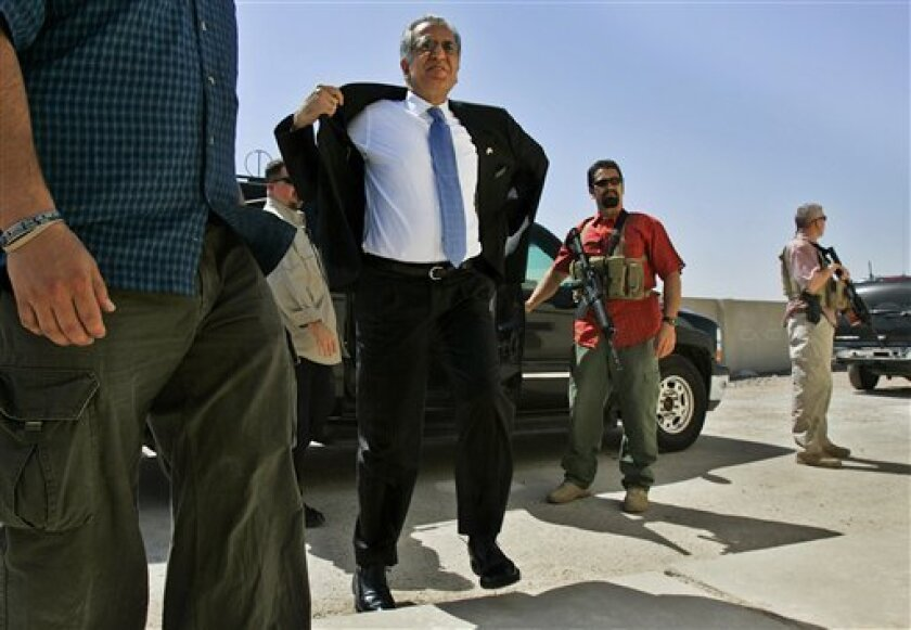 FILE - In this Saturday, March 25, 2006 file photo, Blackwater security contractors guard former U.S. ambassador to Iraq, Zalmay Khalilzad, center, as he arrives at a community sports center in Baghdad, Iraq. The U.S. Embassy has confirmed that the security firm once known as Blackwater Worldwide finished its work in Baghdad on Thursday, May 6, 2009. The company become a flashpoint for Iraqi anger after contractors killed 17 civilians in Baghdad in 2007. (AP Photo/Jacob Silberberg, File)