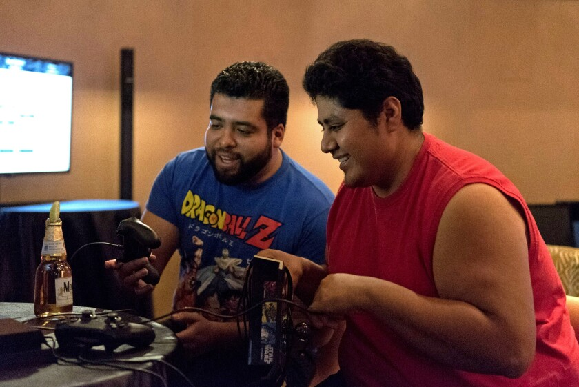 """Felipe Sarmiento, left, and Angel Trejo compete in a """"Street Fighter V"""" tournament at the Downtown Grand's e-sports lounge in Las Vegas last month."""