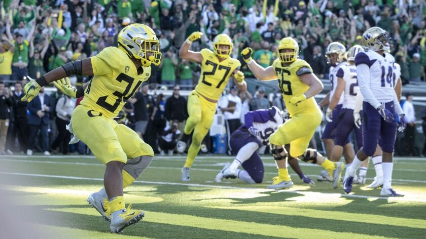Oregon running back CJ Verdell (34), scores the winning touchdown in overtime to beat Washington 30-27 on Saturday.