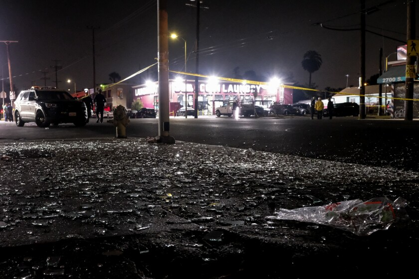 Broken glass litters the street after a cache of illegal fireworks exploded in a South Los Angeles neighborhood June 30.
