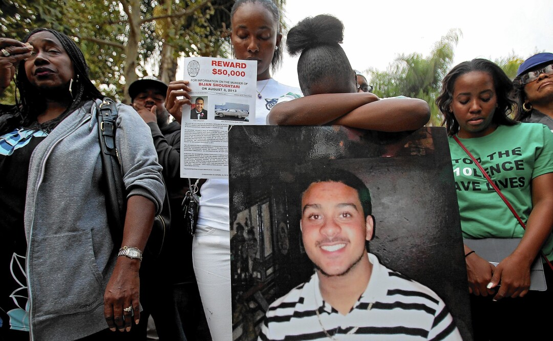 Mourners carry a photo of a man who was killed