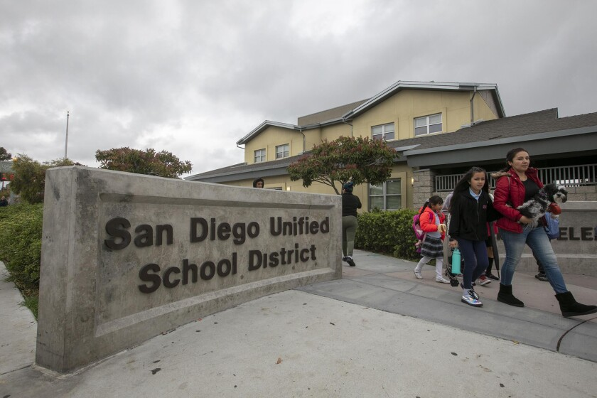 Students walk past the San Diego Unified School District sign in March 2020.