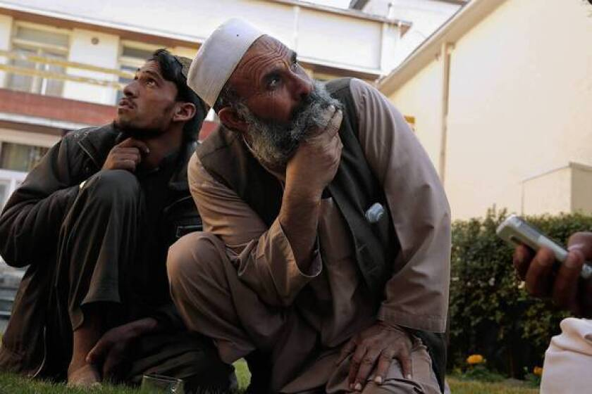 Abdul Ghafar, left, and Rahmat Gul, who both lost relatives in a U.S. drone attack in their Afghan village Sept. 7, watch as a U.S. drone flies over the city of Jalalabad.
