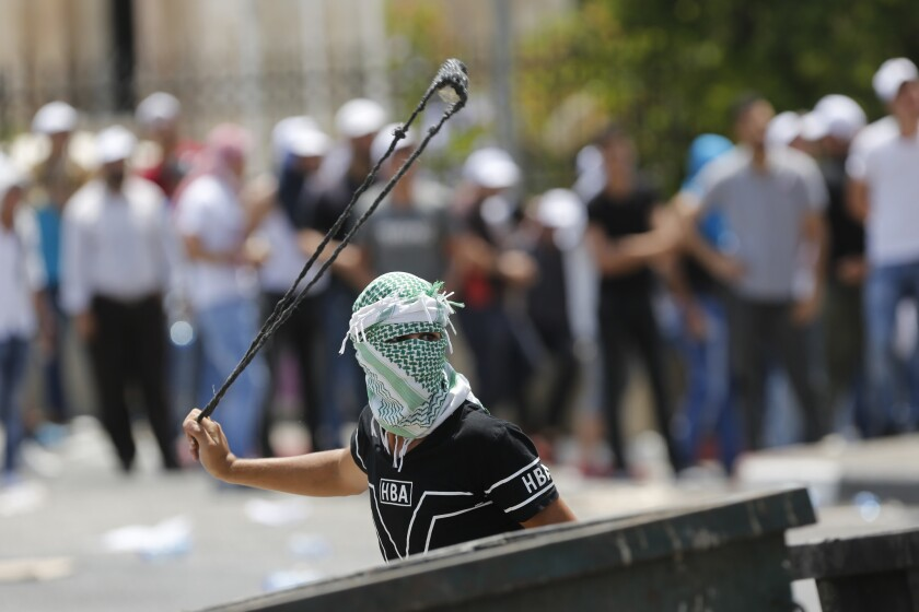 A Palestinian uses a slingshot against Israeli soldiers during clashes in the West Bank city of Bethlehem, Friday, July 21, 2017. Israel police severely restricted Muslim access to a contested shrine in Jerusalem's Old City on Friday to prevent protests over the installation of metal detectors at the holy site.