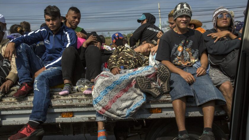 Central American migrants traveling on a flat bed trailer arrive in Queretaro, Mexico, Saturday, Nov. 10, 2018.