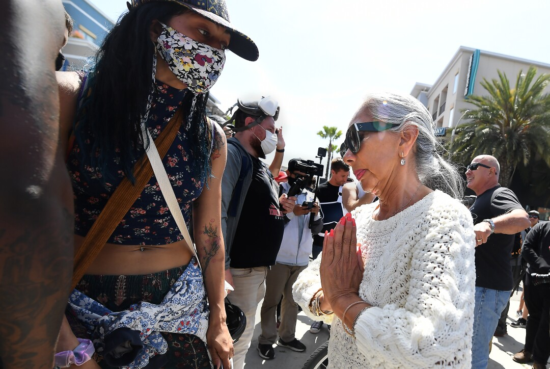 A woman clasps her hands as she talks to a Black Lives Matter supporter