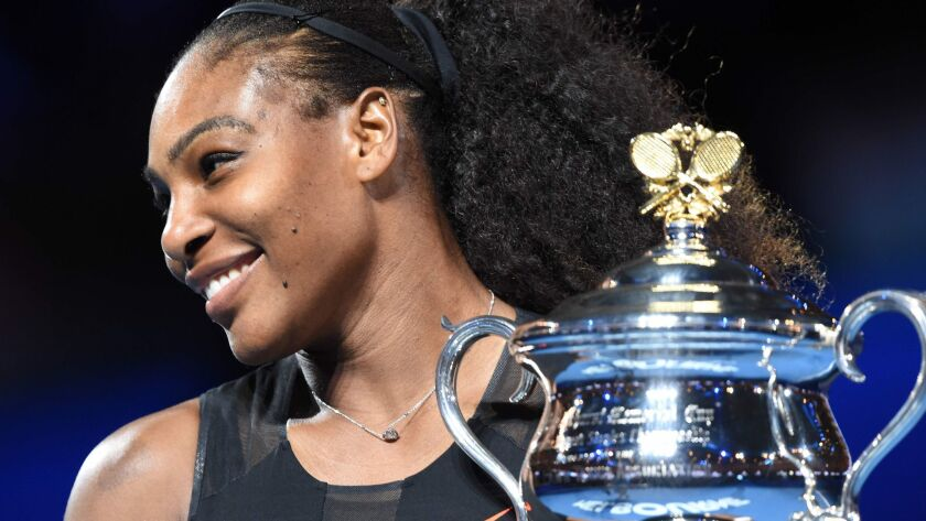 Serena Williams holds up the winner's trophy following her victory over sister Venus Williams in the Australian Open women's singles championship match on Jan. 28, 2017.