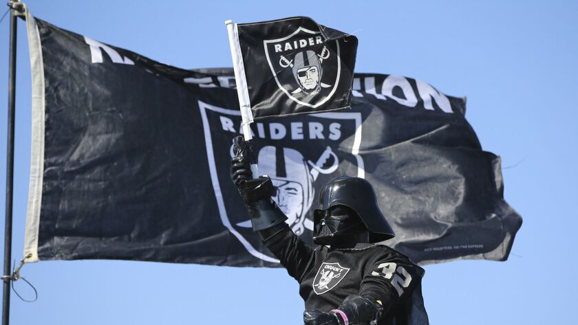 An Oakland Raiders fans holds up a flag while tailgating before the start of an NFL football game ag