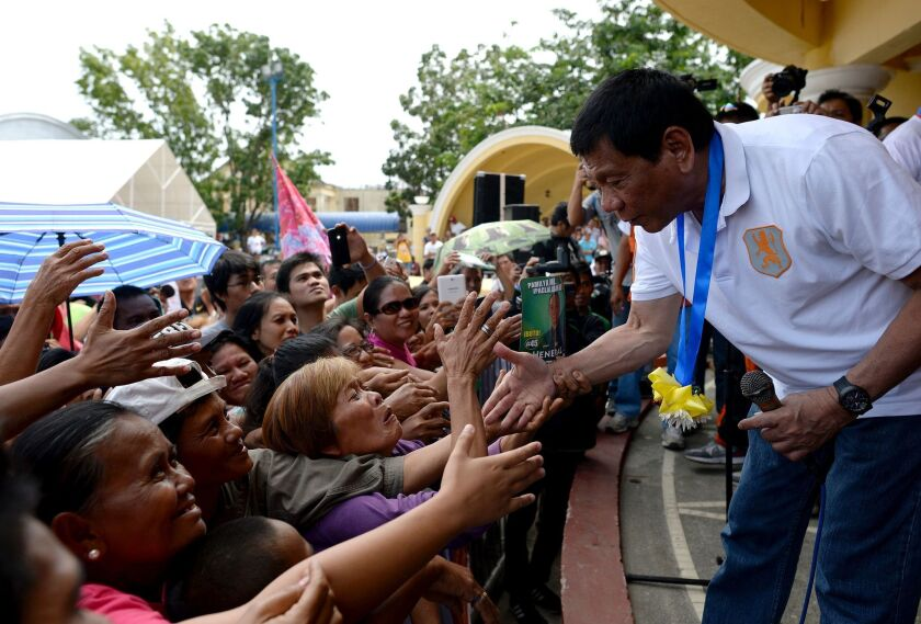 Davao City Mayor and presidential candidate Rodrigo Duterte shakes hands with supporters in Lingayen, Philippines, on March 2.