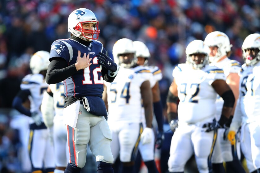Tom Brady gestures toward the sideline during a playoff game against the Chargers.