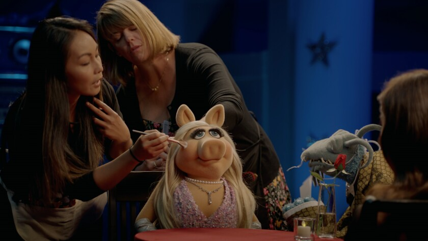 """Miss Piggy gets a touch-up during an interview with Aubrey Plaza on the Disney+ series """"Muppets Now."""""""
