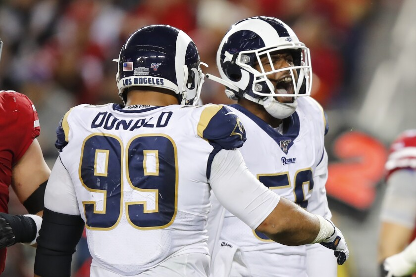 Rams linebacker Dante Fowler Jr. celebrates with teammate Aaron Donald after recording one of six second-half sacks of 49ers quarterback Jimmy Garoppolo on Dec. 21, 2019.