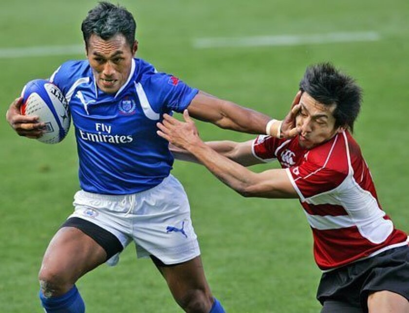 Uale Mai (left) of Samoa gets past Kaoru Matsushita of Japan during a USA Sevens rugby tournament match yesterday at Petco Park. Matches continue today. (K.C. Alfred / Union-Tribune)