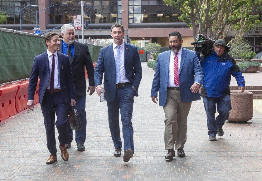 Former US Representative Duncan Hunter, center, walks towards Broadway after leaving through the back door of the Federal courthouse in San Diego, CA on March 17th after being sentenced to 11 months in Federal Prison after pleading guilty to a single count related to campaign fraud.