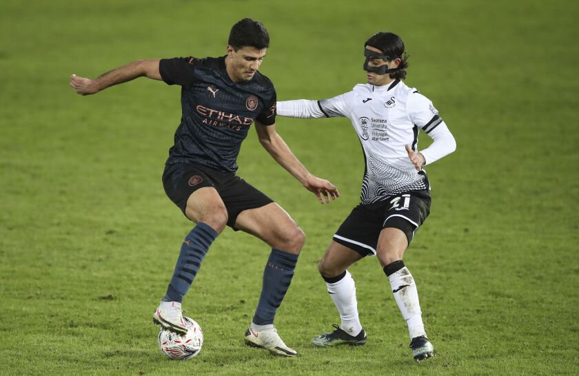 Manchester City's Rodri, left, and Swansea City's Yan Dhanda battle for the ball during the English FA Cup fifth round soccer match at Liberty Stadium, Swansea, Wales, Wednesday Feb. 10, 2021. (Nick Potts/PA via AP)