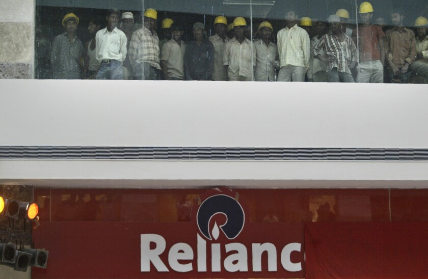 FILE- In this Oct. 11, 2007 file photo, construction workers watch the opening of Reliance Retail's first apparel specialty store in Gurgaon, India. India's Reliance Retail Ventures has set a franchise agreement with 7-Eleven, Inc., to launch convenience stores in the second most populous nation, the company said Thursday. (AP Photo/Mustafa Quraishi, File)