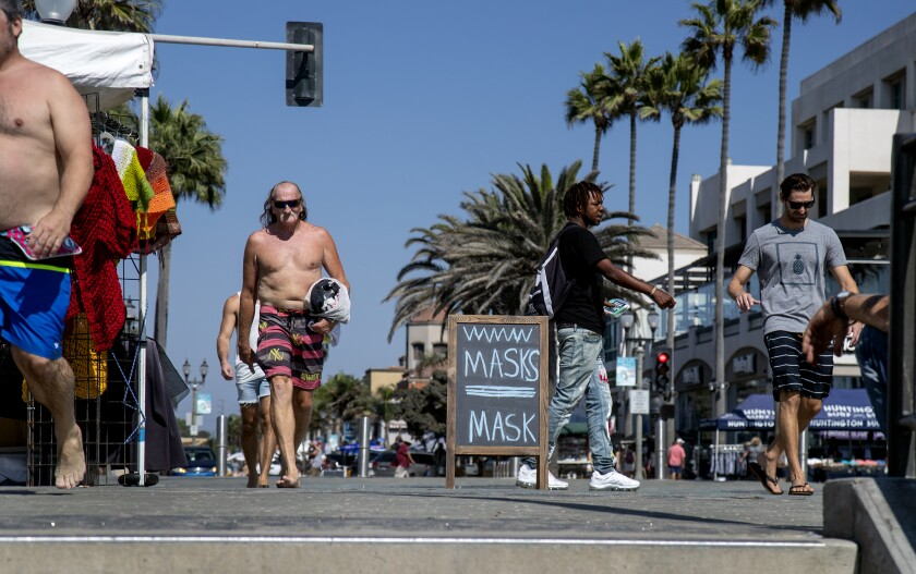 People aren't wearing masks near the pier in Huntington Beach.