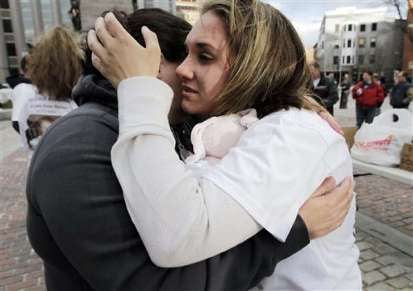 Trista Reynolds, right, mother of missing toddler Ayla Reynolds, is overcome by grief as she is hugged by friend, Laurie Boissonneault, of Biddeford, Maine, during a gathering in Portland, Maine, on Wednesday, April 4, 2012. About 100 people held a vigil to mark the second birthday of the girl who disappeared from her father's home just days before Christmas. (AP Photo/Pat Wellenbach)