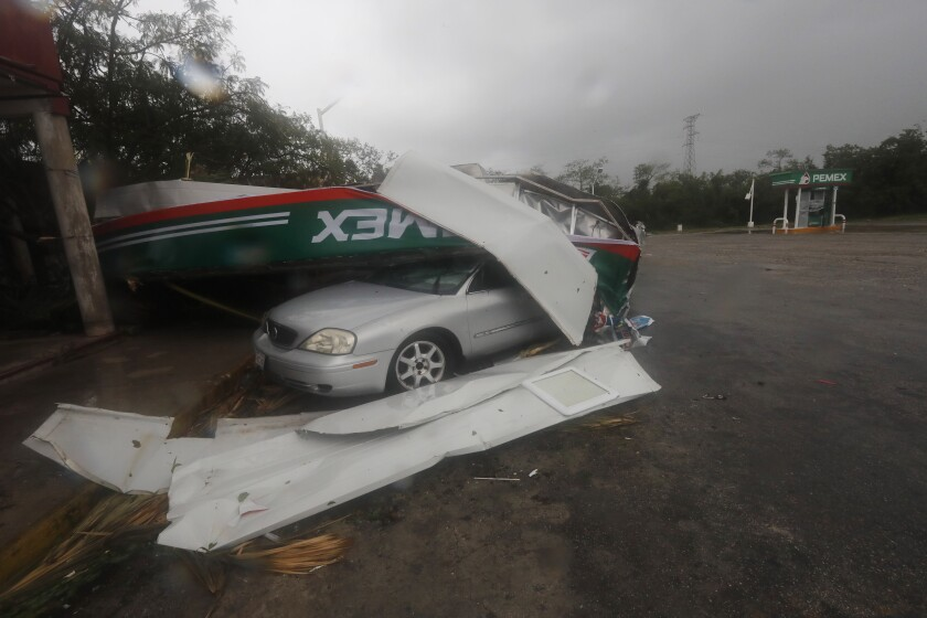 A car is crushed under a metallic structure amid Hurricane Grace in Playa del Carmen, Mexico.