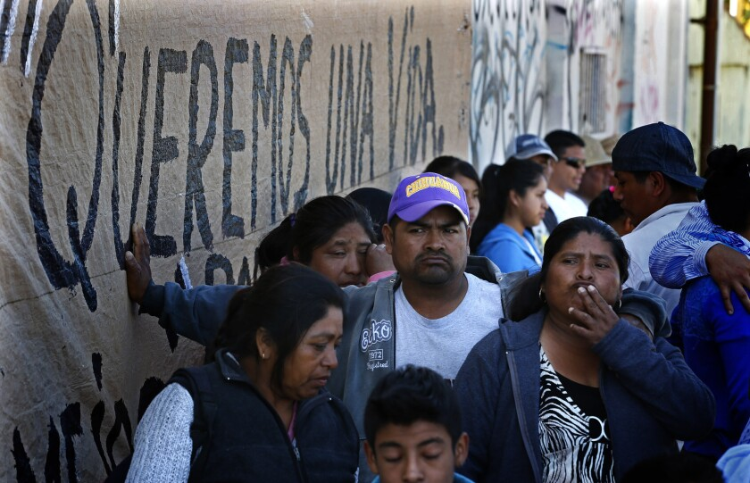 "Tension shows on the faces of striking Mexican farmworkers in Baja California on Wednesday as they wait for news about ongoing salary negotiations that are now in their second week. A hand-painted sign on the wall reads in Spanish, ""We want a life."""