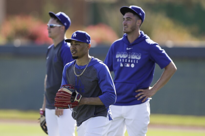 Dodgers right fielder Mookie Betts, center, waits with center fielder Cody Bellinger, right, and outfielder Joc Pederson, during spring training baseball Wednesday, Feb. 19, 2020, in Phoenix.
