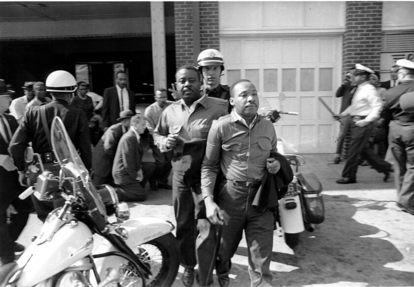 The Rev. Martin Luther King Jr., right, being hauled off to the Birmingham, Ala., jail on April 12, 1963. Behind him: The Rev. Ralph Abernathy.