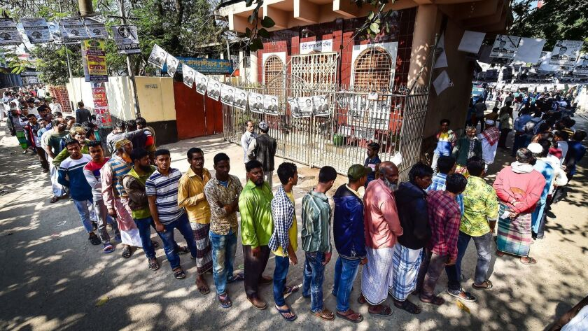 Bangladeshi voters wait in line outside a polling station in Dhaka.