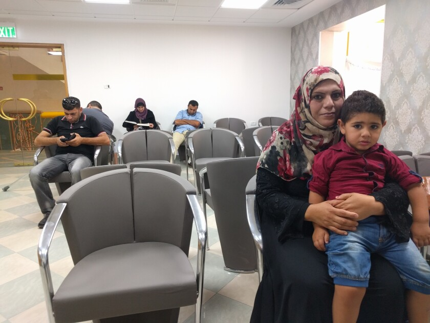 Fathiya Safadi sits in the waiting room of the Razan fertility clinic in Nablus with son Amir, who was conceived with seminal fluid smuggled out of an Israeli prison from her husband, Amir.