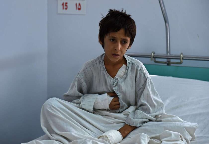 A wounded Afghan boy, survivor of the U.S. airstrikes on a hospital in Kunduz, sits on his bed at an Italian aid organization hospital in Kabul on Oct. 6.
