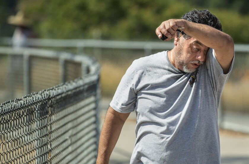 Miguel Garcia of Tujunga wipes the sweat off of his face Friday after jogging at Hansen Dam Recreation Area in Pacoima.