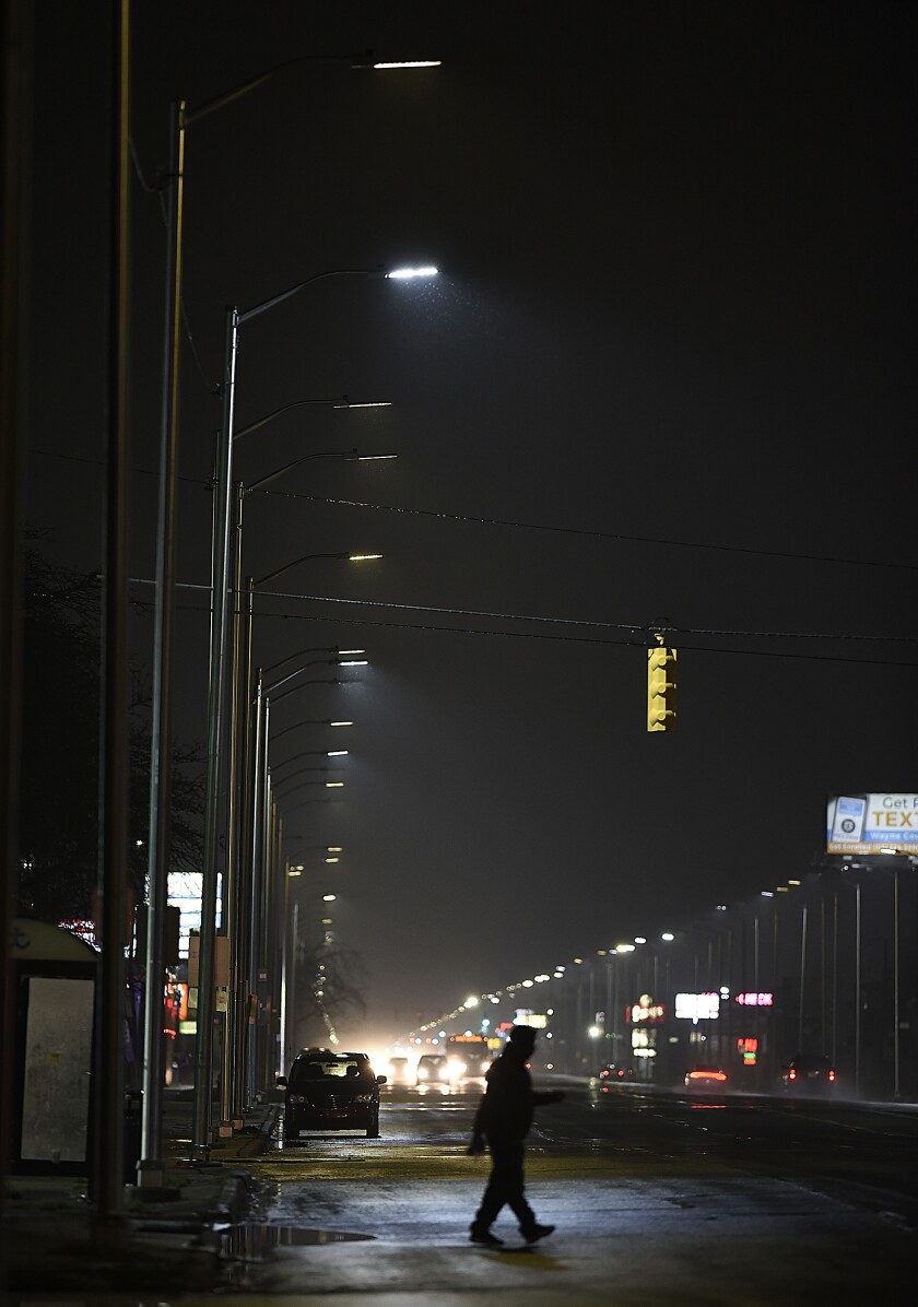 FILE - In this May 2, 2019, file photo, a pedestrian crosses Gratiot Street at Outer Drive East under a bright streetlight flanked by dimmer streetlights in Detroit. Leotek Electronics USA has agreed to pay $4 million to settle a lawsuit with Detroit over thousands of defective streetlights in Detroit, a newspaper reported. The city sued the company last spring, alleging that roughly 20,000 lights were failing.(Clarence Tabb Jr./Detroit News via AP, File)