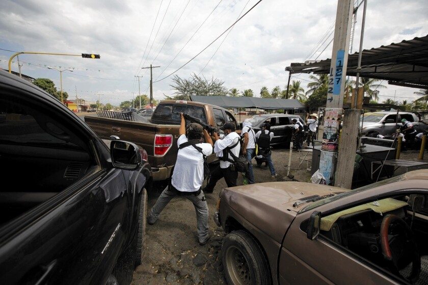 Vigilantes hold Mexico town, tenuously, after driving out cartel