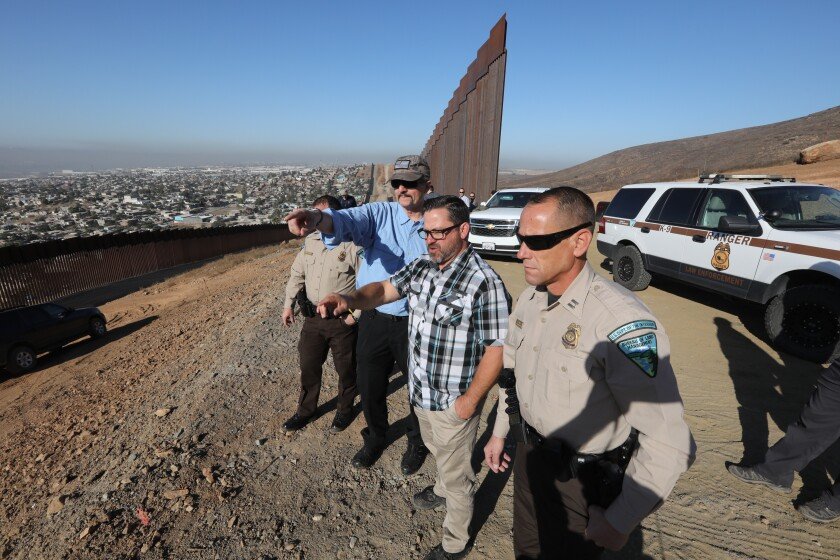 William Perry Pendley, second from left, acting director of the Bureau of Land Management, visited the U.S.-Mexico border at Otay Mesa in San Diego on Tuesday. He is briefed by BLM Senior Law Enforcement Officer Chris Rice, far left, BLM Special Agent Brad Kent, second from right, and BLM Chief Law Enforcement Officer for the Palm Springs-South Coast Field Office Scott Kotlowski, far right.